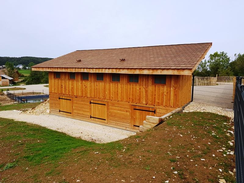 On voit ici l'arrière des toilettes sèches et ces 7 fenêtres carré et en dessous des toilettes on voit la grande chambre de compostage et ces 3 portes d'accès