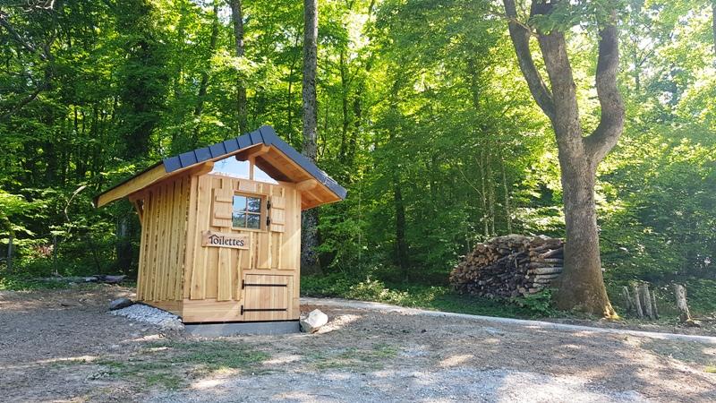 Une toilette sèche installée à coté d'un tas de bois