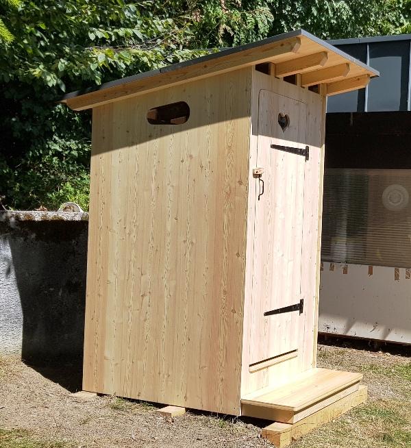 On voit la toilette ESTIVE vue de coté dans le jardin