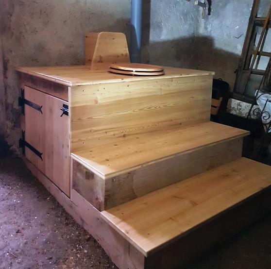Deux marches pour acceder à la toilette sèche avec son abattant le tout installée dans la cave d'une ferme en Haute-Savoie